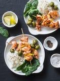 Spiedi e riso di color salmone - tavola sana del pranzo Spiedo di color salmone arrostito del pesce su un fondo scuro fotografie stock