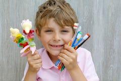 Spiedo della caramella gommosa e molle della tenuta del ragazzo del bambino in una mano e spazzolini da denti in un altro Fotografie Stock Libere da Diritti