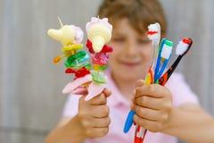 Spiedo della caramella gommosa e molle della tenuta del ragazzo del bambino in una mano e spazzolini da denti in un altro Fotografia Stock Libera da Diritti