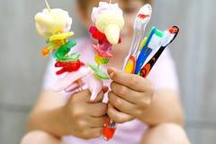 Spiedo della caramella gommosa e molle della tenuta del ragazzo del bambino in una mano e spazzolini da denti in un altro Fotografie Stock