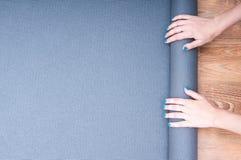 Spiegare una stuoia di yoga Fotografie Stock