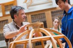 Spiegazione dell'insegnante in una classe della lavorazione del legno Immagini Stock