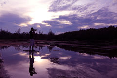 Spiegel der purpurroten Himmelreflexion zum Wasser mit Schatten des Fotografen Lizenzfreies Stockfoto