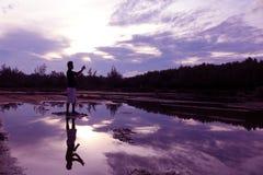 Spiegel der purpurroten Himmelreflexion zum Wasser mit Schatten des Fotografen Stockbilder