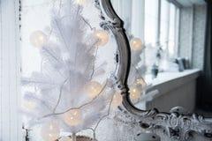 Spiegel in einem alten Rahmen und in einem Baum der weißen Weihnacht Lizenzfreie Stockfotografie