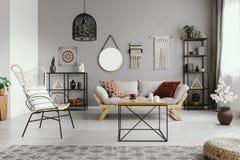 Spiegel, Makramee und Grafik auf der grauen Wand warmen ethno Wohnzimmers lizenzfreie stockbilder