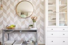Spiegel op gevormd behang boven grijze lijst met bloemen in s royalty-vrije stock fotografie