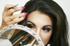 Spiegel reflektieren Kosmetik und Make-upmaterial, schönes Mädchen tut ihr Make-up, Handbewegung, rosa Lidschatten und netten gro Lizenzfreie Stockbilder