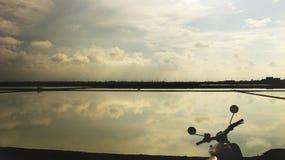 Spiegel-Reflexion des Himmels und der Wolken im Wasser mit Schattenbild des Weinlese-Motorrads - Seesalz-Bauernhof Thailand lizenzfreies stockbild
