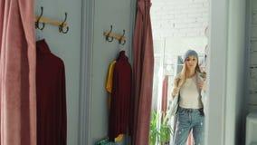 Spiegel van het jonge meisje proberen op kleren in montageruimte die wordt geschoten Zij draagt denimjasje, jeans en hoed, gladma stock video