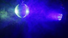 Spiegelbal voor disco op een zwarte achtergrond in de stralen van verlichting stock video