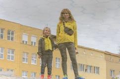 Spiegelbezinning in het water van moeder en dochter royalty-vrije stock afbeeldingen