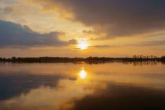 Spiegelbezinning in rivier van zonsondergang met mooie hemel royalty-vrije stock fotografie