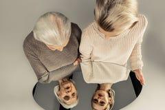 Spiegelbezinning van jonge en oude vrouwen royalty-vrije stock foto
