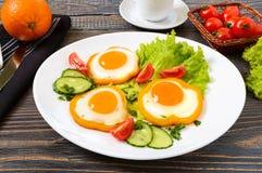 Spiegelei in einem Kreis des Gemüsepaprikas auf einer weißen Platte mit Frischgemüse, ein Tasse Kaffee, frische Orangen auf einem Stockfotografie