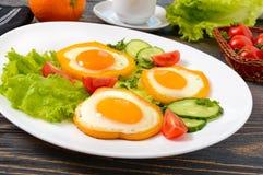 Spiegelei in einem Kreis des Gemüsepaprikas auf einer weißen Platte mit Frischgemüse, ein Tasse Kaffee, frische Orangen auf einem Lizenzfreies Stockfoto