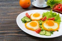 Spiegelei in einem Kreis des Gemüsepaprikas auf einer weißen Platte mit Frischgemüse, ein Tasse Kaffee, frische Orangen auf einem Stockfoto