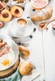 Spiegelei mit Würsten und Speck, Brot, Hörnchen, Kaffee Stockfotos