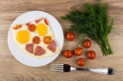 Spiegelei mit Wurst in der Platte, in den Tomaten, im Dill und in der Gabel Stockfotografie