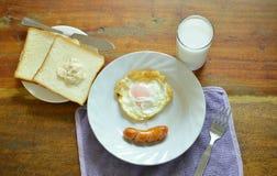 Spiegelei und Schweinswurst mit Brot essen Paarmilch-Frühstückssatz Lizenzfreie Stockfotos