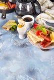 Spiegeleier des englischen Frühstücks, Würste, Toast, Tomaten auf Steintabelle Stockfotografie
