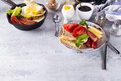 Spiegeleier des englischen Frühstücks, Würste, Toast, Tomaten auf Steintabelle Stockbild
