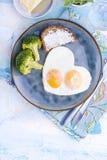 Spiegeleier in Form von Innerem Auf einer dunklen Platte mit blauer Schale des Brokkolis und des Toasts mit Tee, Äpfel, Butter zu Lizenzfreie Stockbilder