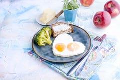 Spiegeleier in Form von Innerem Auf einer dunklen Platte mit blauer Schale des Brokkolis und des Toasts mit Tee, Äpfel, Butter zu Lizenzfreies Stockbild