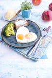 Spiegeleier in Form von Innerem Auf einer dunklen Platte mit blauer Schale des Brokkolis und des Toasts mit Tee, Äpfel, Butter zu Lizenzfreie Stockfotografie