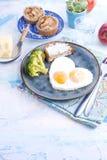 Spiegeleier in Form von Innerem Auf einer dunklen Platte mit blauer Schale des Brokkolis und des Toasts mit Tee, Äpfel, Butter zu Lizenzfreie Stockfotos