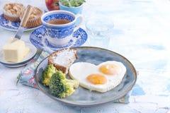 Spiegeleier in Form von Innerem Auf einer dunklen Platte mit blauer Schale des Brokkolis und des Toasts mit Tee, Butter zum Frühs Stockbild