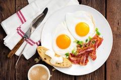 Spiegeleier, Speck und italienisches ciabatta Brot auf weißer Platte Tasse Kaffee Draufsicht des Frühstücks Hölzerner Hintergrund lizenzfreies stockbild