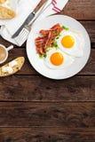 Spiegeleier, Speck und italienisches ciabatta Brot auf weißer Platte Tasse Kaffee Draufsicht des Frühstücks Hölzerner Hintergrund lizenzfreie stockbilder