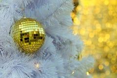Spiegeln Sie goldene Weihnachtsballeinzelteile auf weißer Torte und gelbem Beleuchtungshintergrund bokeh Form LED wider Lizenzfreie Stockfotos