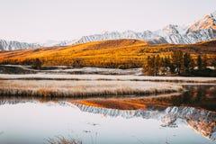 Spiegeloppervlakte en pieken van de rotsen van het meer in de bergvallei stock fotografie