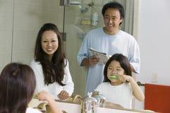 Spiegelreflexion der Familie im Badezimmer, das zu bürstenden Zähnen der Tagestochter fertig wird Lizenzfreie Stockbilder