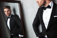 Spiegelreflexion des entspannten jungen Mannes, der ein schwarzes Smoking trägt lizenzfreies stockfoto