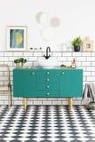 Spiegels en affiche boven groen kabinet in badkamersbinnenland met gouden stoel en installaties Echte foto royalty-vrije stock fotografie