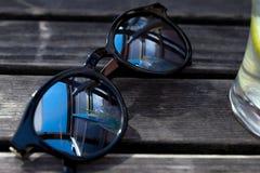 Spiegelsonnenbrille auf Holztisch Stockbild