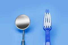 Spiegeltandarts en tandenborstel op een blauwe achtergrond Stock Fotografie