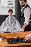 spiegelweerspiegeling van kapper het voorbereidingen treffen om haar van te snijden stock afbeeldingen