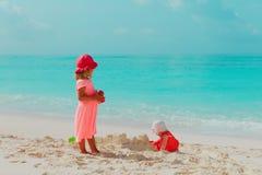 Spiel der kleinen M?dchen mit Sand auf Strand stockfotografie
