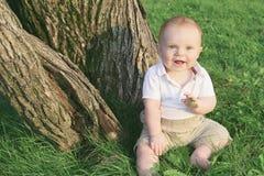 Spiel des kleinen Jungen im grünen Gras Lizenzfreie Stockfotos