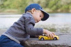Spiel des kleinen Jungen mit einem Auto Lizenzfreie Stockfotos