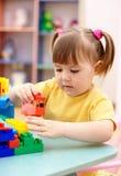 Spiel des kleinen Mädchens mit Gebäudeziegelsteinen im Vortraining stockfotografie