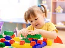 Spiel des kleinen Mädchens mit Gebäudeziegelsteinen im Vortraining Stockbild