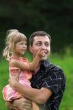 Spiel des kleinen Mädchens mit Vati in der Natur Stockbild