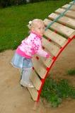 Spiel des recht kleinen Mädchens auf Spielplatz im Park. Lizenzfreie Stockfotografie