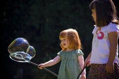 Spiel mit zwei jungen Mädchen mit Luftblasen. Stockbild