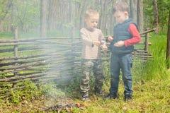 Spiel mit zwei Jungen neben einem rauchenden Feuer stockbild